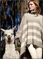 Model wearing our Suri Alpaca and Wool Snow Drift Poncho poses with a camelid, a special guest at our last photo shoot in Peru